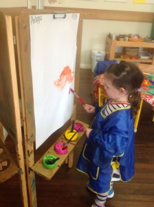 Philippa (G) painting at the easel.